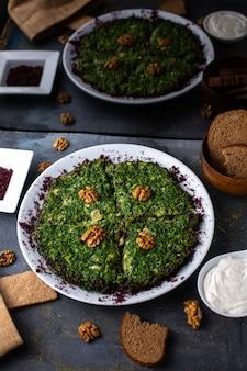 Une vue de face salade de poulet aux noix et verts à l'intérieur de la plaque blanche avec des miches de pain chips sur le bureau gris légume salade mayyonaise