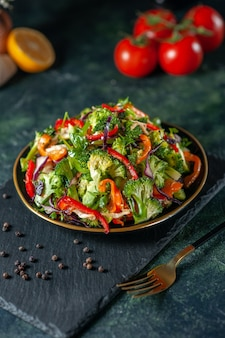 Vue de face d'une salade végétalienne avec des ingrédients frais dans une assiette et du poivre sur une planche à découper noire