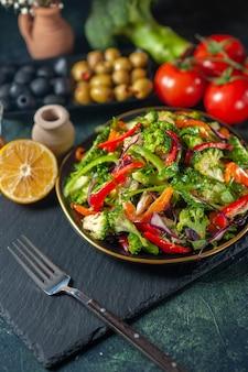 Vue de face d'une salade végétalienne avec des ingrédients frais dans une assiette sur une planche à découper noire