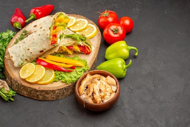 Vue de face sandwich à la viande de shaurma en tranches avec des tranches de citron et des verts sur un espace sombre