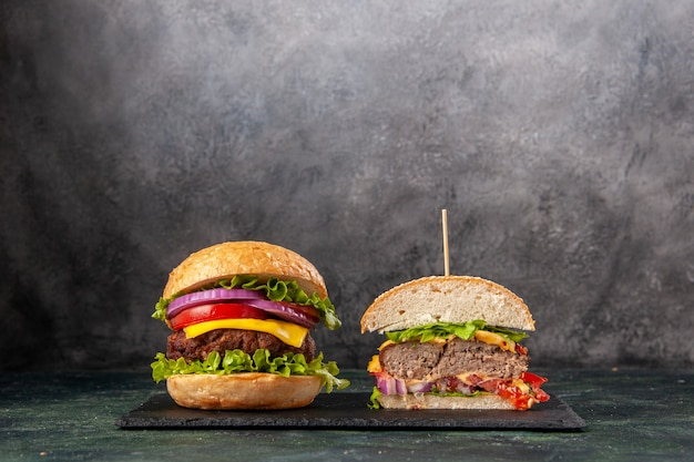 Vue de face de sandwichs savoureux entiers coupés sur un plateau noir sur une surface de couleur sombre