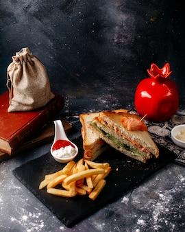 Vue de face des sandwichs tranchés avec des frites sur le bureau noir et le sol gris