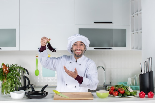 Vue de face satisfait chef masculin en uniforme tenant une aubergine dans la cuisine
