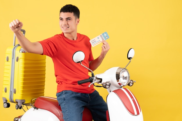 Vue de face satisfait jeune homme dans des vêtements décontractés sur un billet de maintien cyclomoteur