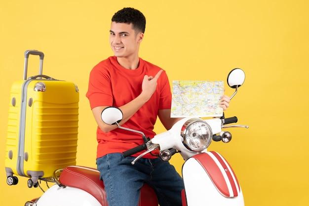 Vue de face satisfait jeune homme dans des vêtements décontractés sur un cyclomoteur tenant une carte de voyage