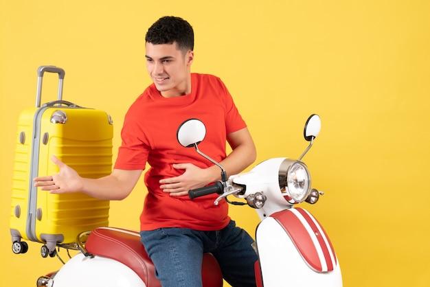 Vue de face satisfait jeune homme en vêtements décontractés sur cyclomoteur donnant la main