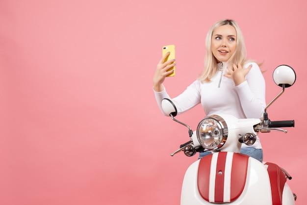 Vue de face satisfaite jeune femme sur cyclomoteur tenant le téléphone