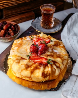 Vue de face savoureuse pâtisserie brune délicieuse avec des fraises en tranches rouges sur le bureau blanc