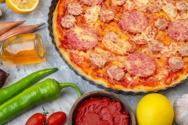 Vue de face savoureuse pizza aux saucisses avec légumes frais sur blanc