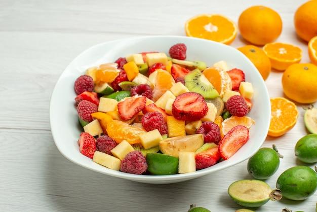 Vue de face savoureuse salade de fruits avec des feijoas et des mandarines fraîches sur un arbre fruité mûr et blanc