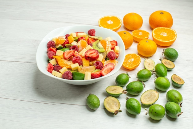 Vue de face savoureuse salade de fruits avec feijoas et mandarines fraîches sur photo de baies mûres blanches arbre fruité moelleux