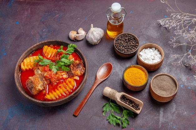 Vue de face savoureuse sauce à la viande avec différents assaisonnements sur une surface sombre sauce plat soupe dîner nourriture
