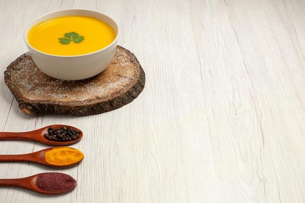 Vue de face savoureuse soupe de citrouille au poivre sur un espace blanc clair