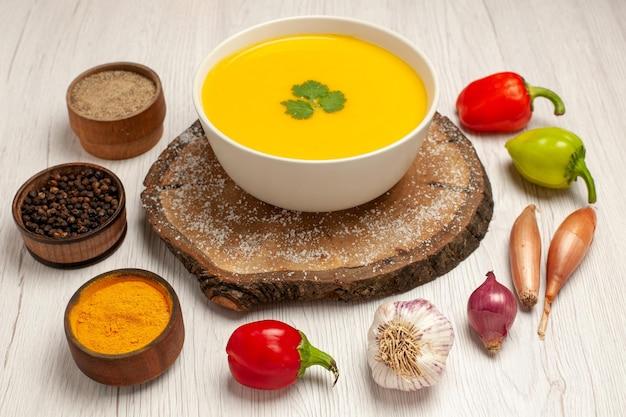 Vue de face savoureuse soupe à la citrouille avec des légumes sur un espace blanc