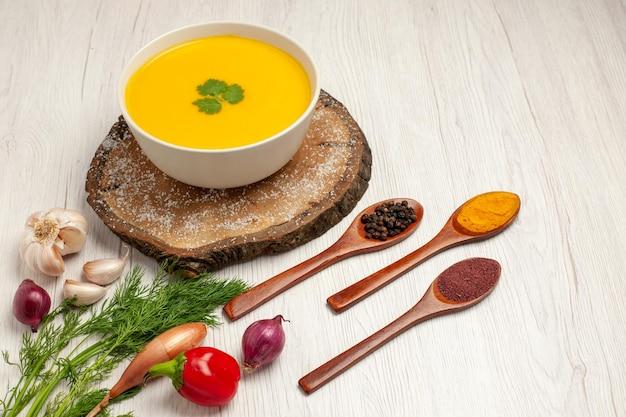 Vue de face savoureuse soupe à la citrouille avec des verts sur un espace blanc clair