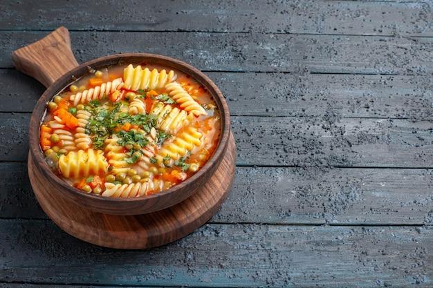 Vue de face savoureuse soupe de pâtes à partir de pâtes italiennes en spirale avec des verts sur le bureau bleu foncé plat de cuisine couleur soupe de pâtes italiennes