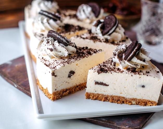 Vue de face savoureux cheesecakes oreo à l'intérieur de la plaque blanche sur la surface brune
