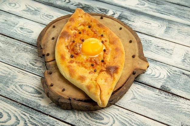 Vue de face savoureux pain aux œufs cuit sur le bureau rustique gris
