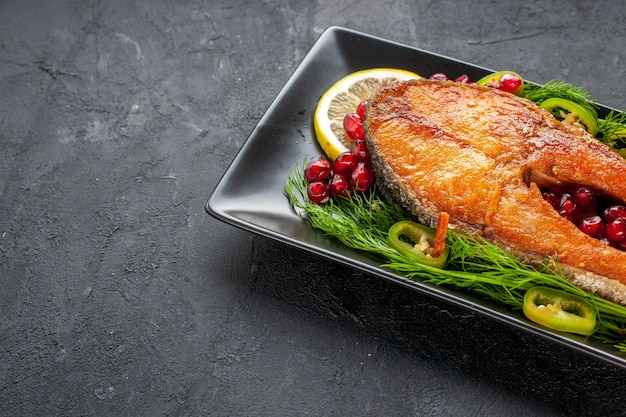 Vue de face savoureux poisson cuit avec des verts et des tranches de citron à l'intérieur de la casserole sur un fond sombre couleur fruits fruits de mer plat photo viande