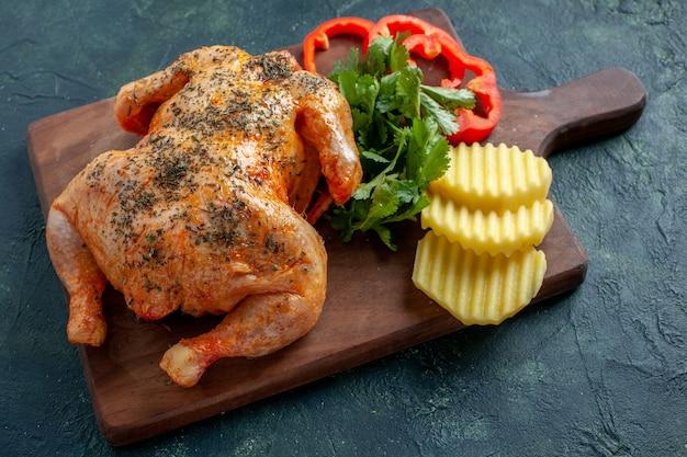 Vue de face savoureux poulet cuit épicé avec des pommes de terre sur une surface sombre