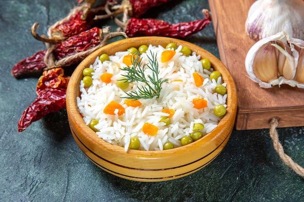 Vue de face savoureux riz bouilli avec du poivre séché et de l'ail