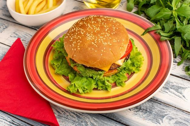 Vue de face savoureux sandwich au poulet avec salade verte et légumes à l'intérieur de la plaque colorée sur un bureau gris rustique.