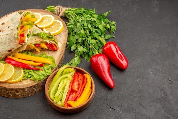 Vue de face savoureux sandwich au poulet tranché shaurma avec du citron et des verts sur un espace sombre