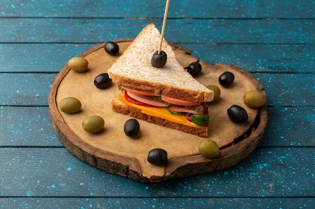 Vue de face savoureux sandwich avec du jambon au fromage à l'intérieur avec des olives sur bleu