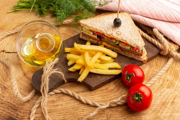Vue de face savoureux sandwich avec tomates jambon d'olive avec frites cordes tomates à l'huile sur bois