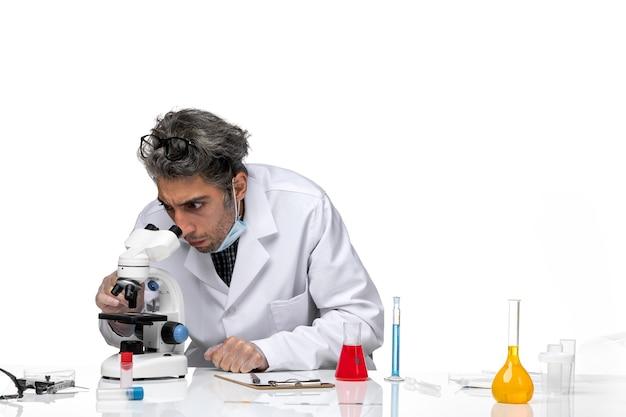 Vue de face scientifique d'âge moyen en combinaison médicale blanche à l'aide d'un microscope