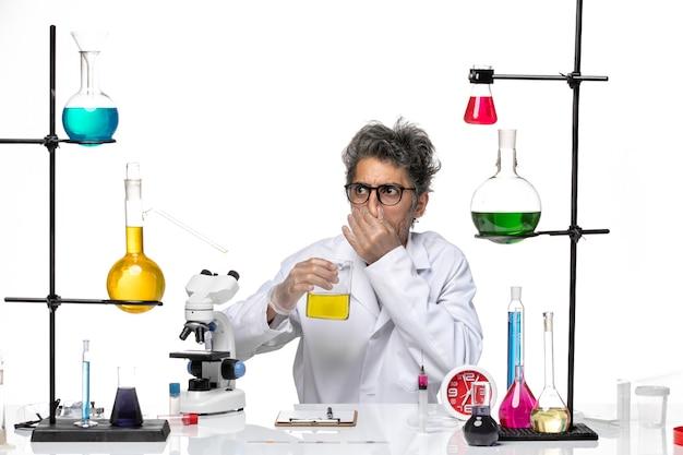 Vue de face scientifique d'âge moyen en combinaison médicale blanche buvant une solution jaune