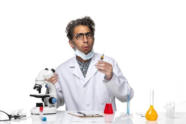 Vue de face scientifique d'âge moyen en combinaison médicale blanche préparant l'injection