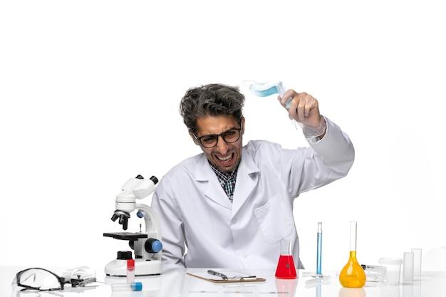 Vue de face scientifique d'âge moyen en combinaison médicale tenant quelque chose