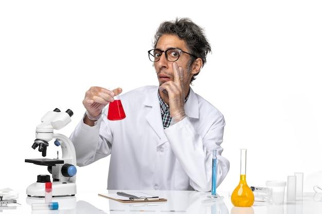 Vue de face scientifique d'âge moyen en combinaison médicale tenant une solution rouge
