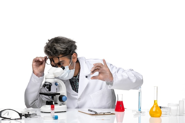 Vue de face scientifique d'âge moyen en combinaison médicale vérifiant petit échantillon au microscope