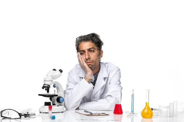 Vue de face scientifique d'âge moyen en costume médical assis autour de la table avec des solutions et de la réflexion