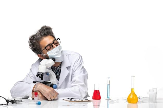 Vue de face scientifique d'âge moyen en costume médical blanc assis et dormant avec un microscope