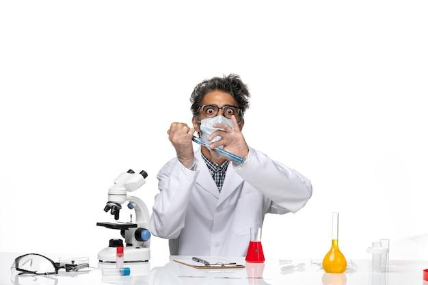 Vue de face scientifique d'âge moyen en costume médical blanc injection de remplissage avec une solution bleue