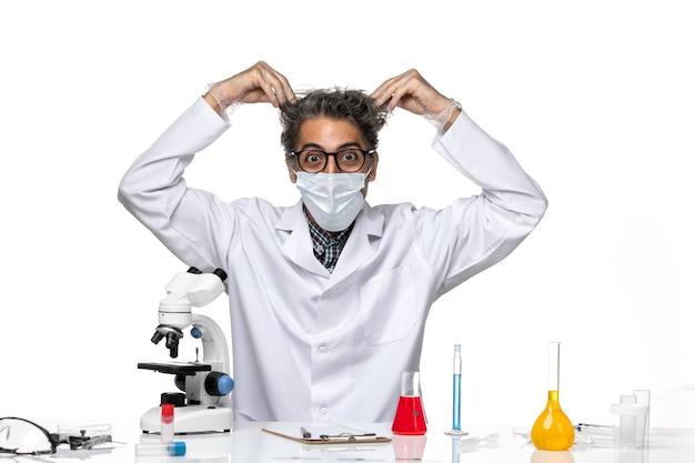 Vue de face scientifique d'âge moyen en costume médical blanc se déchirant les cheveux