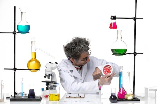 Vue de face scientifique d'âge moyen en costume médical blanc tenant horloge