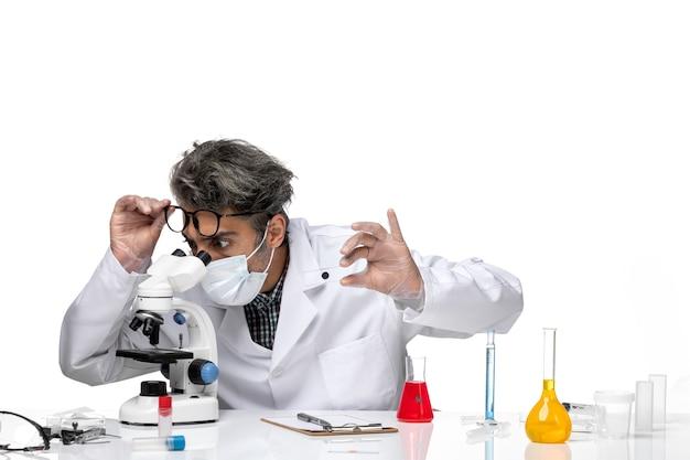 Vue de face scientifique d'âge moyen en costume médical blanc tenant peu d'échantillon le vérifiant