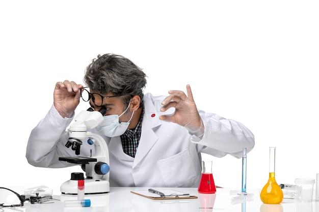 Vue de face scientifique d'âge moyen en costume médical blanc vérifiant petit échantillon