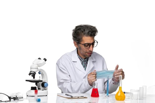 Vue de face scientifique d'âge moyen en costume médical tenant un masque