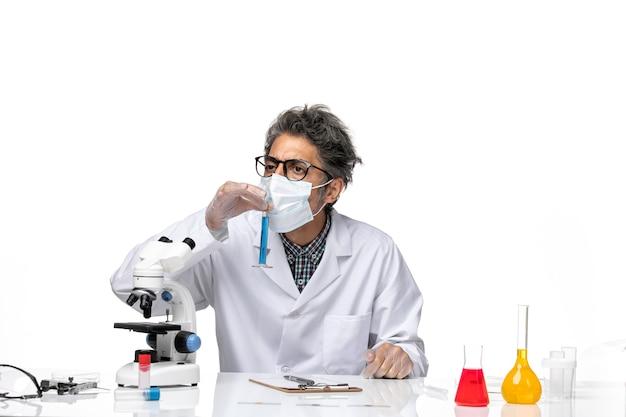 Vue de face scientifique d'âge moyen en costume spécial assis tenant un ballon avec une solution