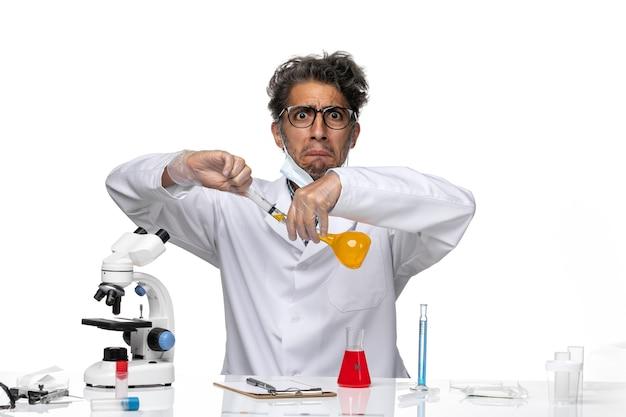 Vue de face scientifique d'âge moyen en injection de remplissage de combinaison médicale blanche