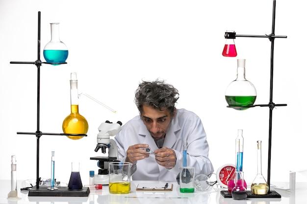 Vue de face scientifique masculin en combinaison médicale travaillant avec injection