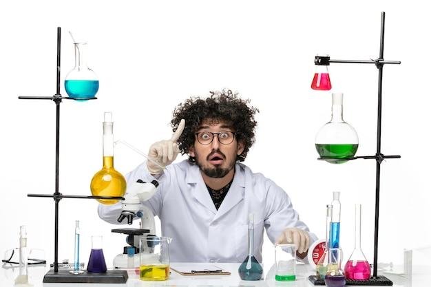 Vue de face scientifique masculin en costume médical assis et posant sur un espace blanc