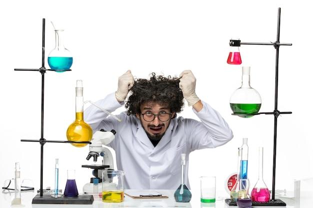 Vue de face scientifique masculin en costume médical assis et se déchirer les cheveux sur un espace blanc