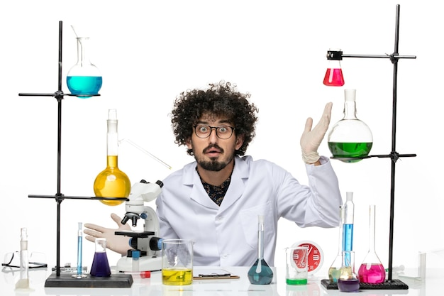 Vue de face scientifique masculin en costume médical assis avec des solutions et un microscope sur un espace blanc