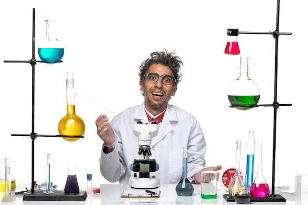 Vue de face scientifique masculin en costume médical blanc souriant